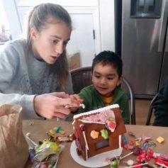 Girl and boy making gingerbread house