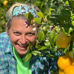 Woman smiling next to lemon tree full of fruit