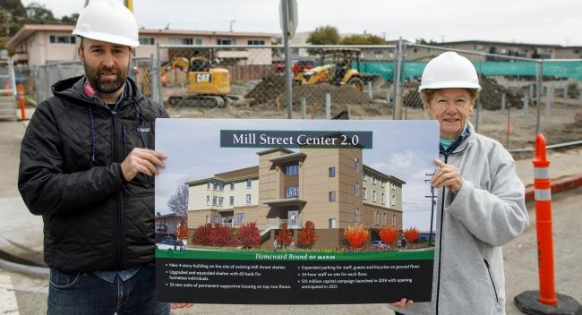Man and woman in hard hats holding sign depicting the future Mill Street Center